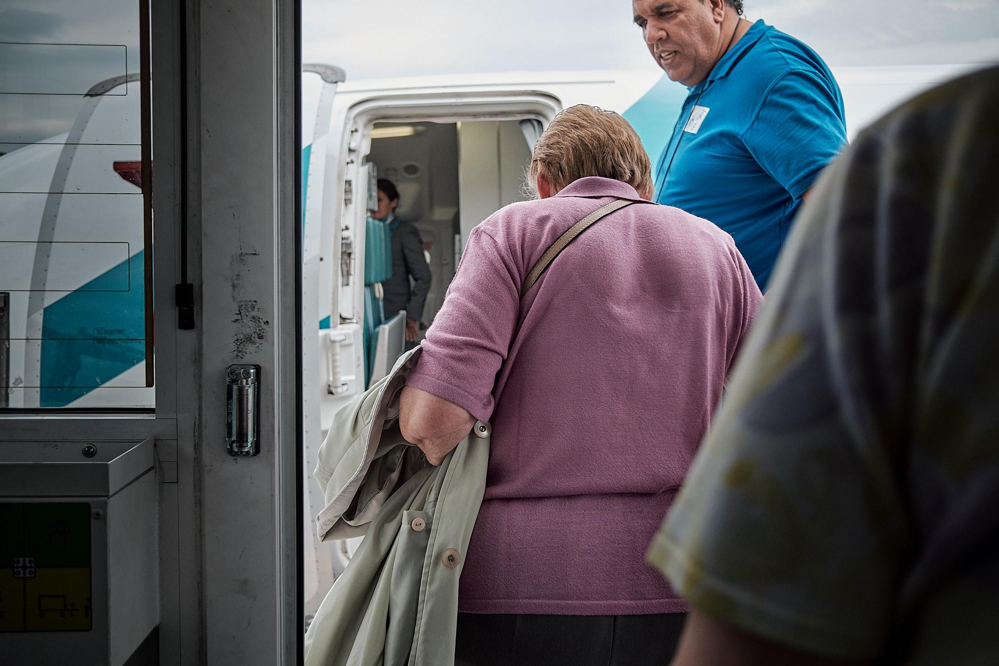 La nonna sta salendo nel suo primo aereo, scortata da un Sansone di due metri… Che servizio!