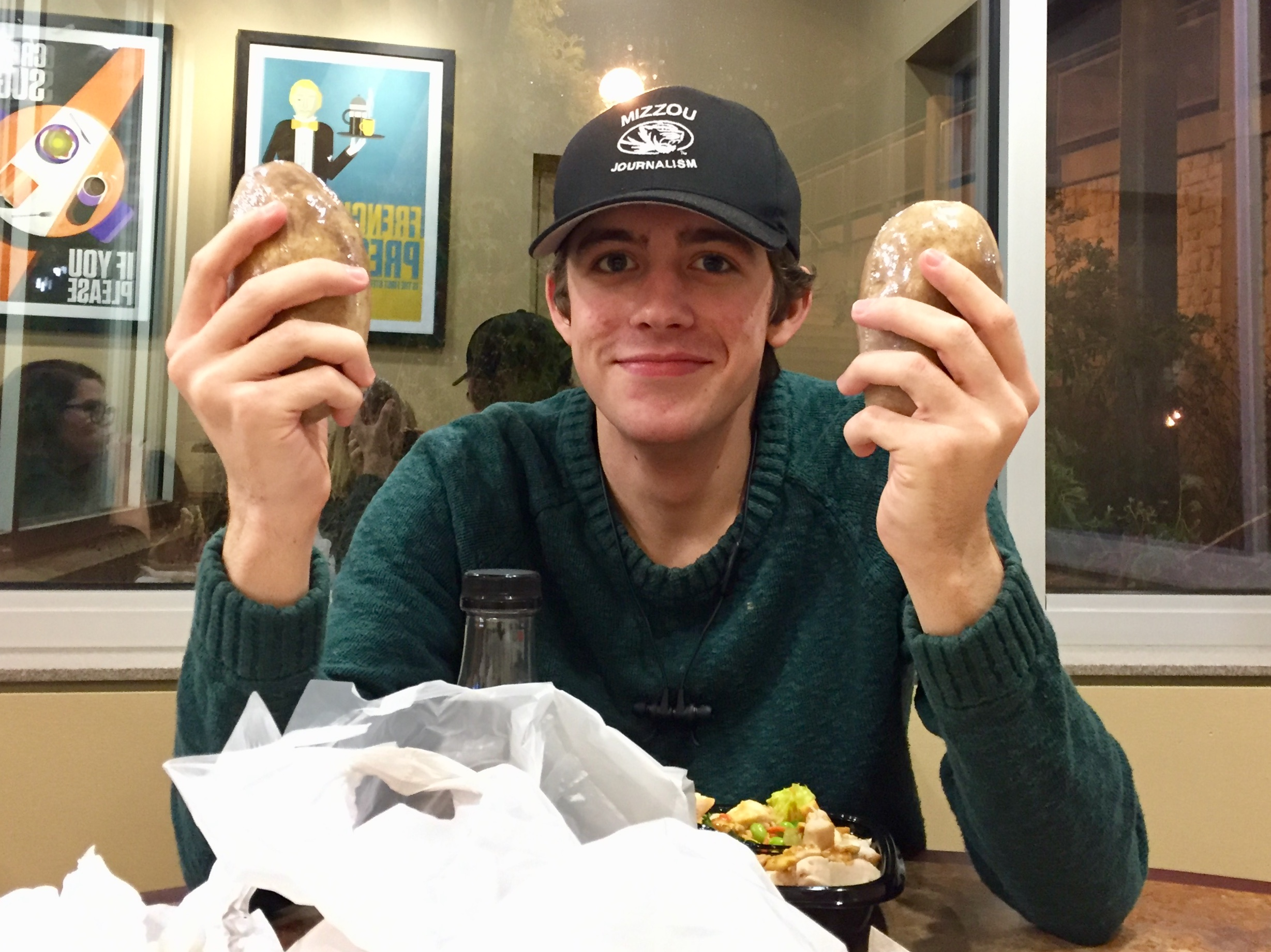 Fellow journalism student Camden Jones showcases his  two  baked potatoes he recently purchased from an on-campus dining hall.