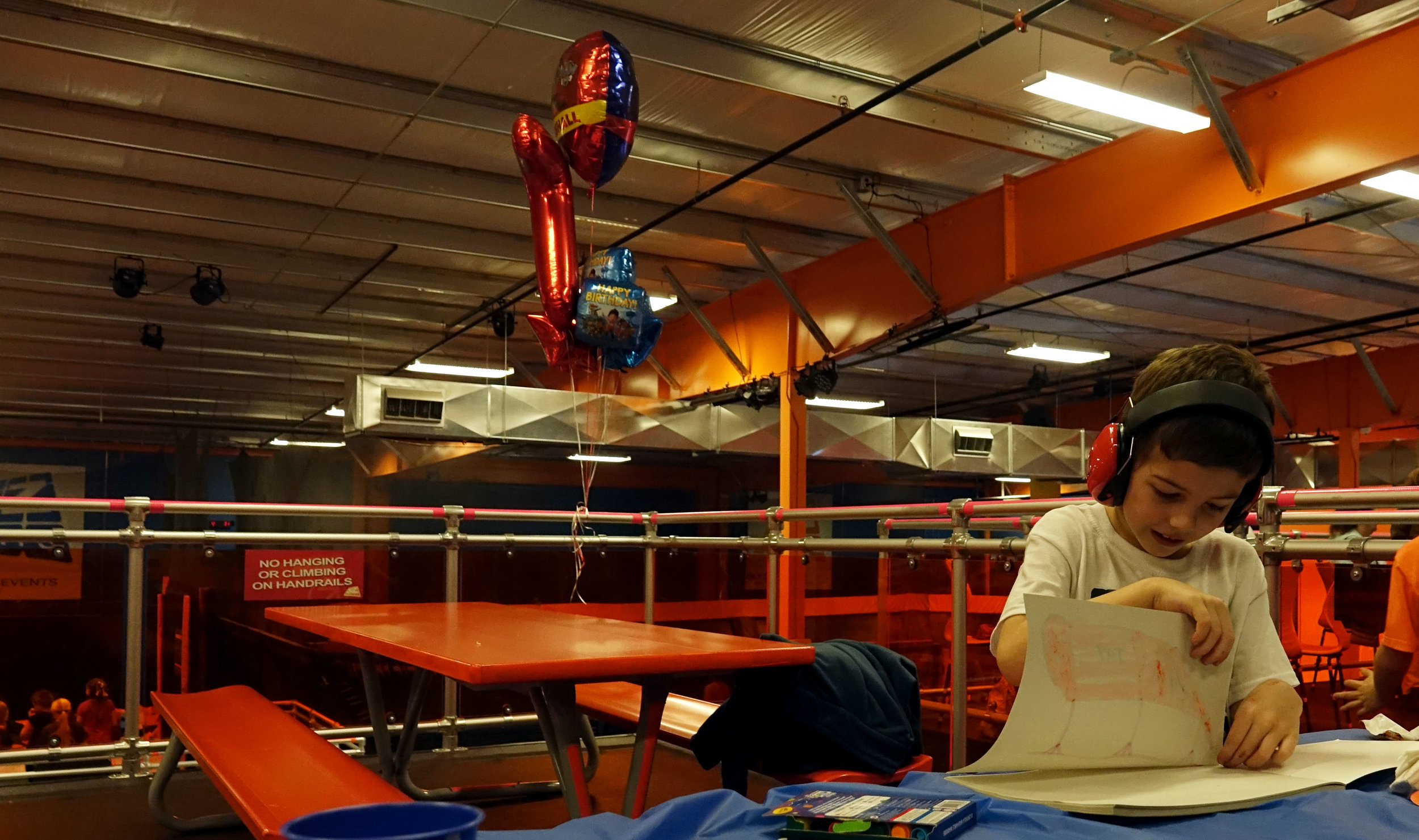 """Jaxon tears a page out of a coloring book during his birthday party at Sky Zone Trampoline Park in Springfield. """"One thing I wish people knew about taking care of a child with autism is that we try our best,"""" Jamie said. """"We do the best we can with what we are given."""" Credit: Kyra Haas / KBIA"""