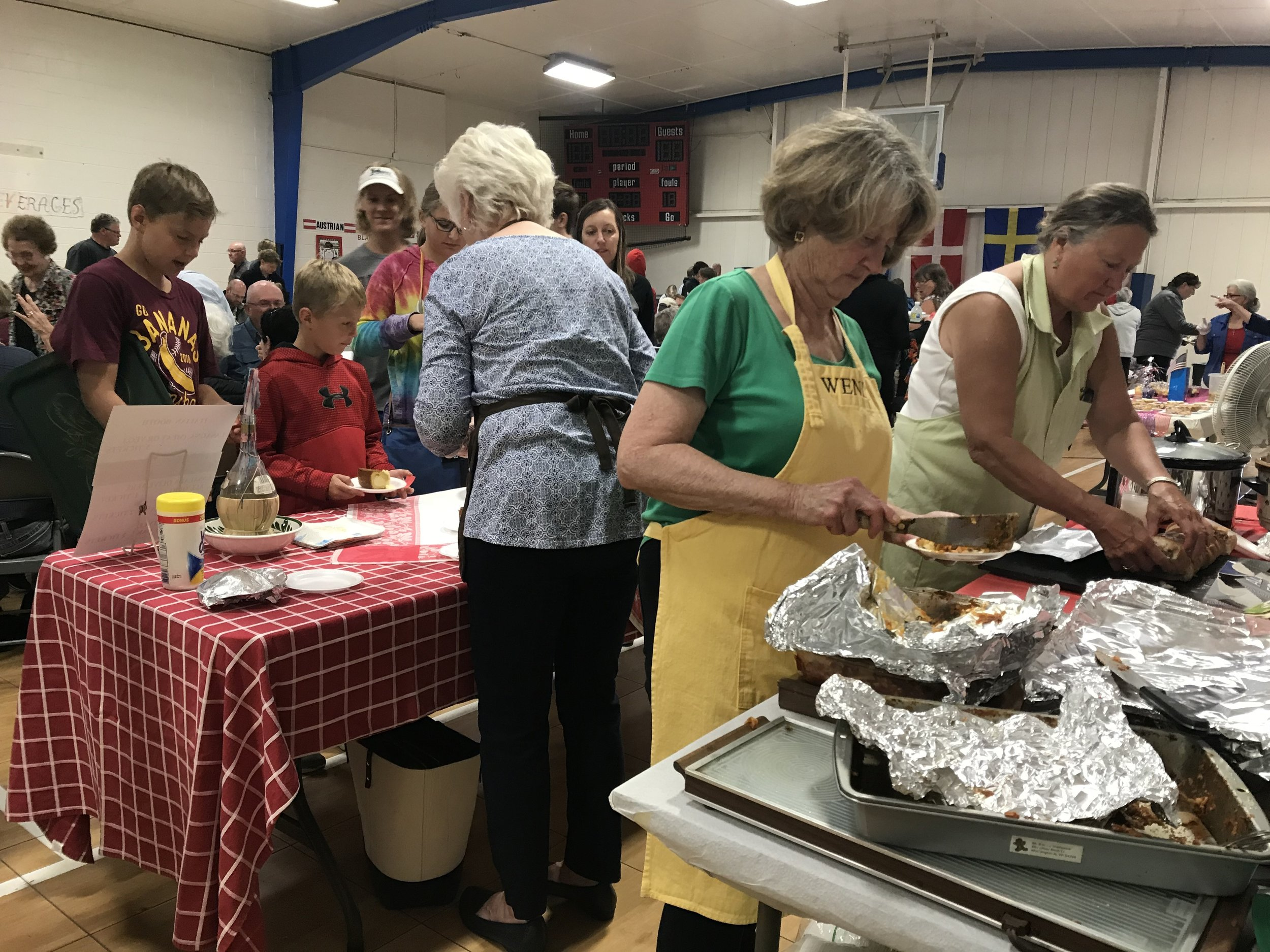 Wendy Cooke, right, serves up lasagna at the Italian booth.