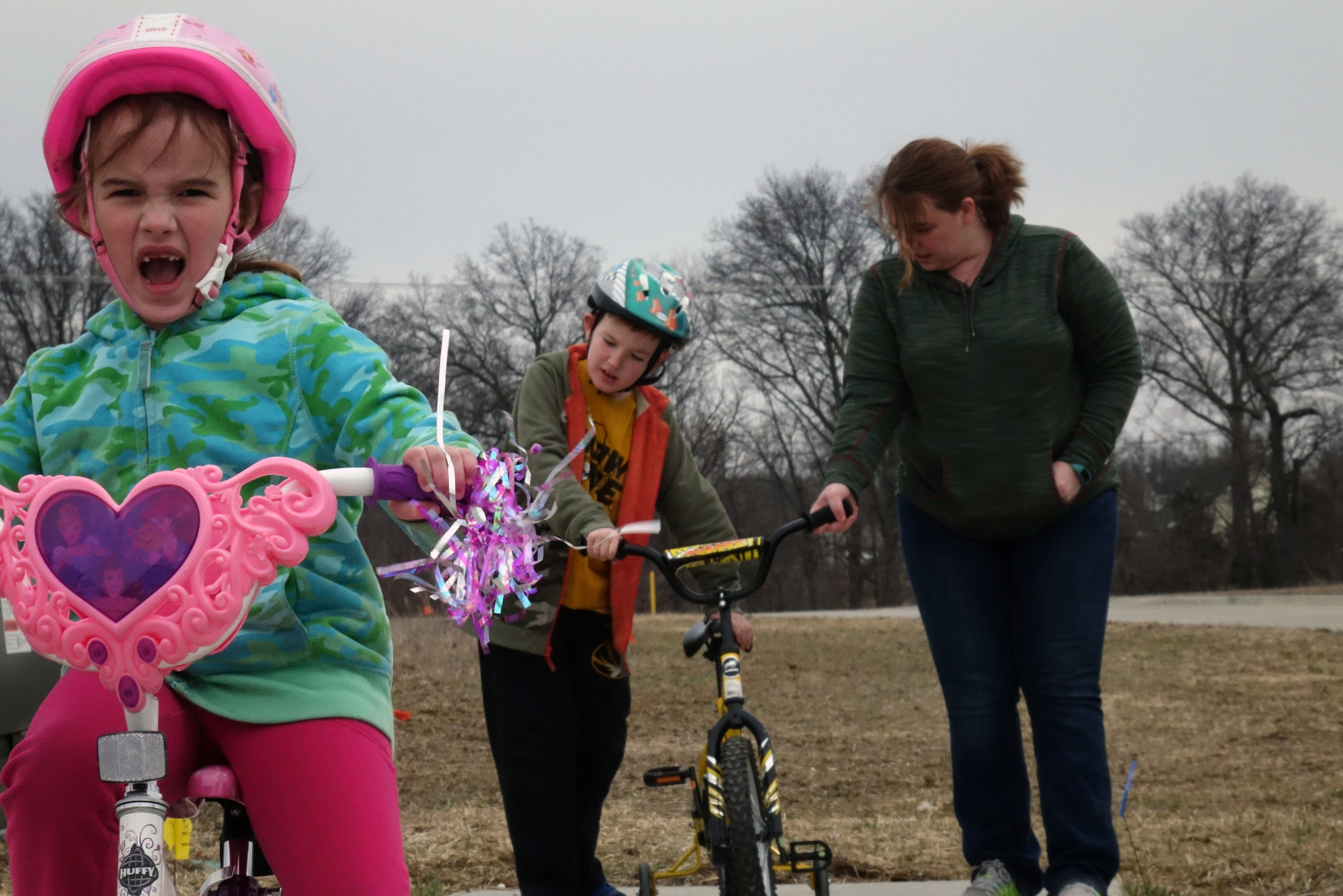 """Regan Arnett, 6, leads the way during a neighborhood bike ride with her brother and mom. """"[Regan and Logan] pretty much coexist,"""" Tara said. """"They will get in each other's world every once in a while, but she moves too fast to wait on him ... It takes him a little bit longer for him to get involved in an activity."""" Credit: Kyra Haas / KBIA"""