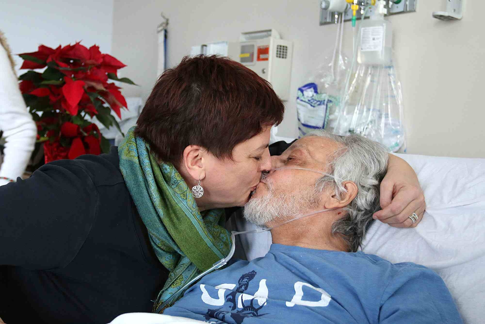 """Maurice """"Frenchie"""" La-Garde kisses his wife, Heike Petermann, at the Whittier Rehabilitation Hospital in Haverhill on Thursday. La-Garde, a quadriplegic since 1987, has overcome a lot in his 61 years, and his family is asking the community for help in making it over one more hurdle: getting back home to North Chelmsford. See video at lowellsun.com. (SUN / JOHN LOVE)  Read more:  http://www.lowellsun.com/breakingnews/ci_31514501/no-mountain-too-high#ixzz50tZwThMI"""