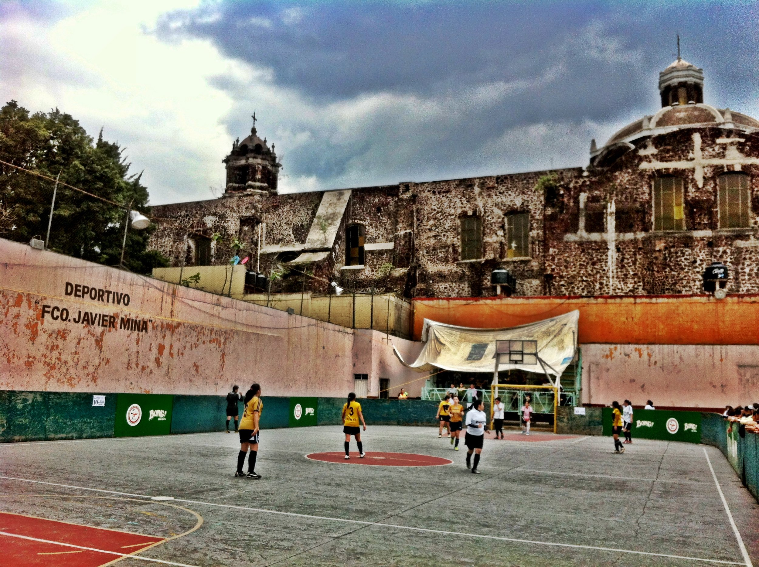 A women's football ream plays in a concrete court in Mexico City