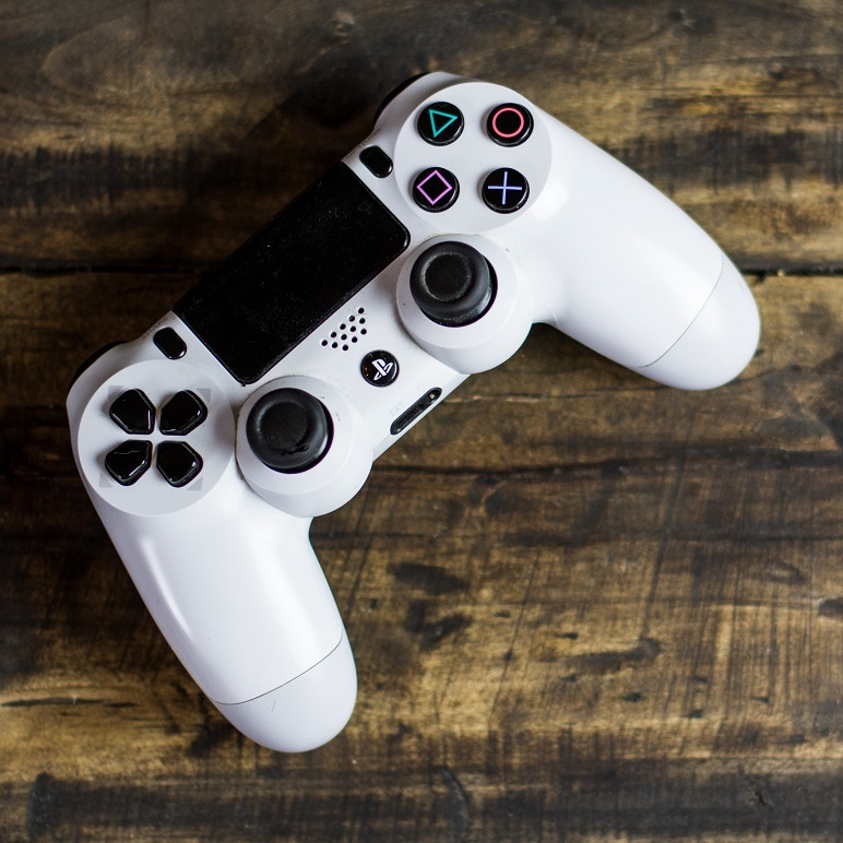 White Sony Ps4 dualshock on wood table. Stock image from Pexels.