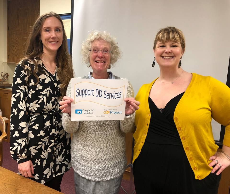 "Three women standing together for a photo at the DD Advocacy Day at the Capitol building in Salem. The woman in the middle holds a sign with the words, ""Support DD Services."" Photo taken by Oregon DD Coalition staff member."