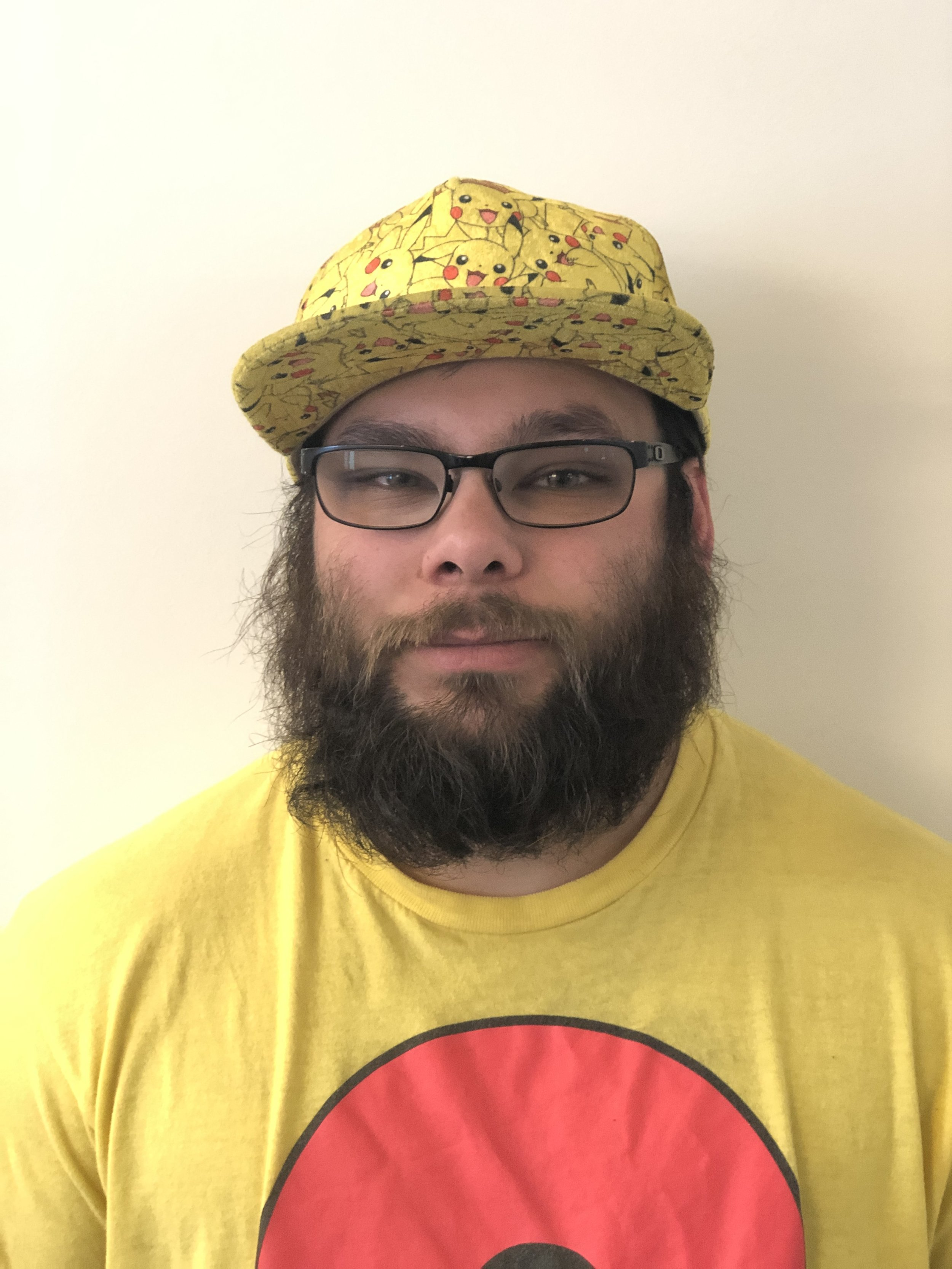 Portrait of Tino wearing a yellow baseball hat with a Pikachu pattern and a matching yellow t-shirt.