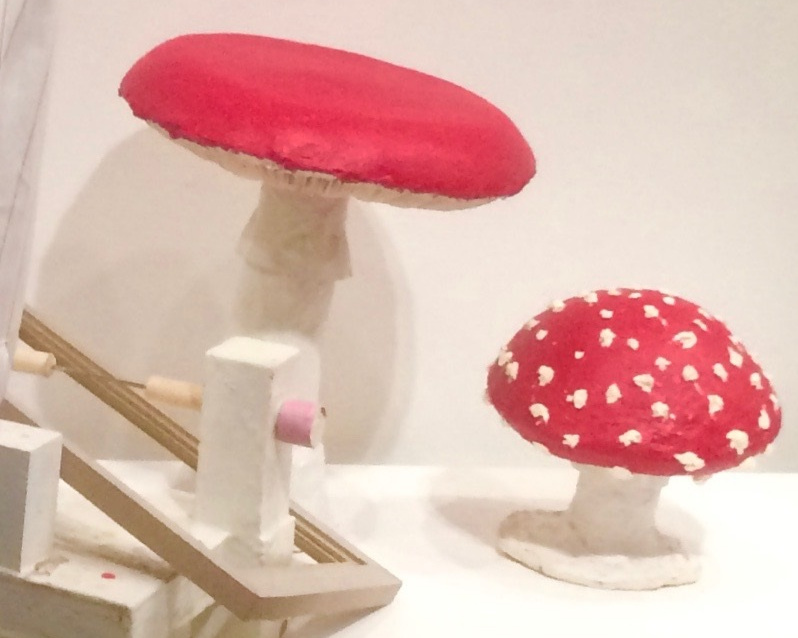 Two red and white mushroom-shaped sculptures by Lawrence featured in an art exhibition. The larger mushroom has a bright red cap, and the smaller one has a bright red cap covered in white dots. Photo courtesy of the artist.