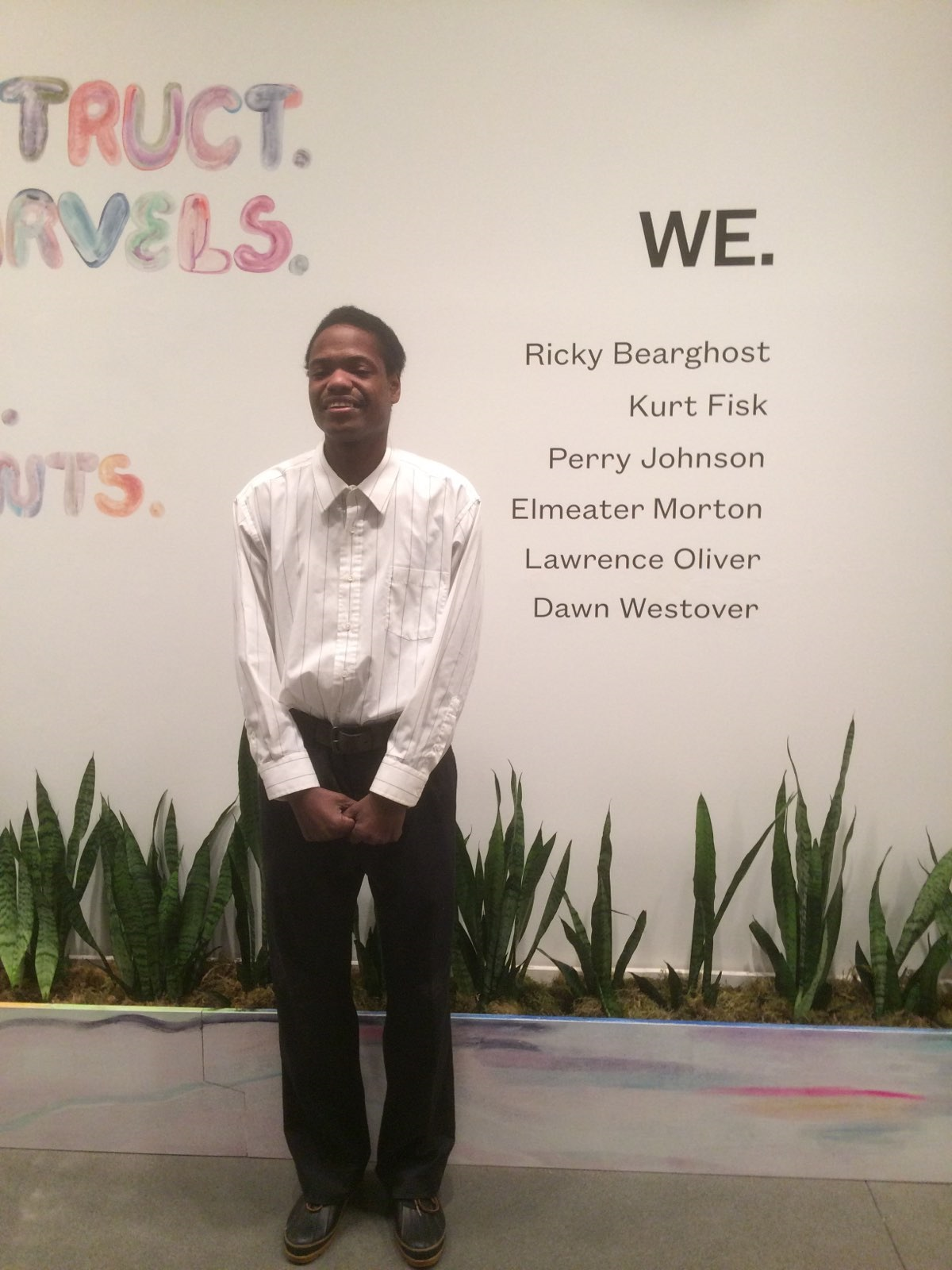 "Lawrence wearing a white button-down shirt and black pants stands in front of a white gallery wall with the decal ""We."" the title of the group exhibition he was featured in at the Portland Art Museum. Photo courtesy of the artist."