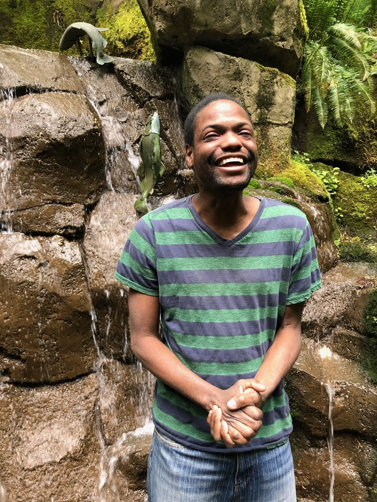 Lawrence smiling widely, clasping his hands together in front of fern and moss covered boulders on a nature walk. Photo courtesy of the artist.