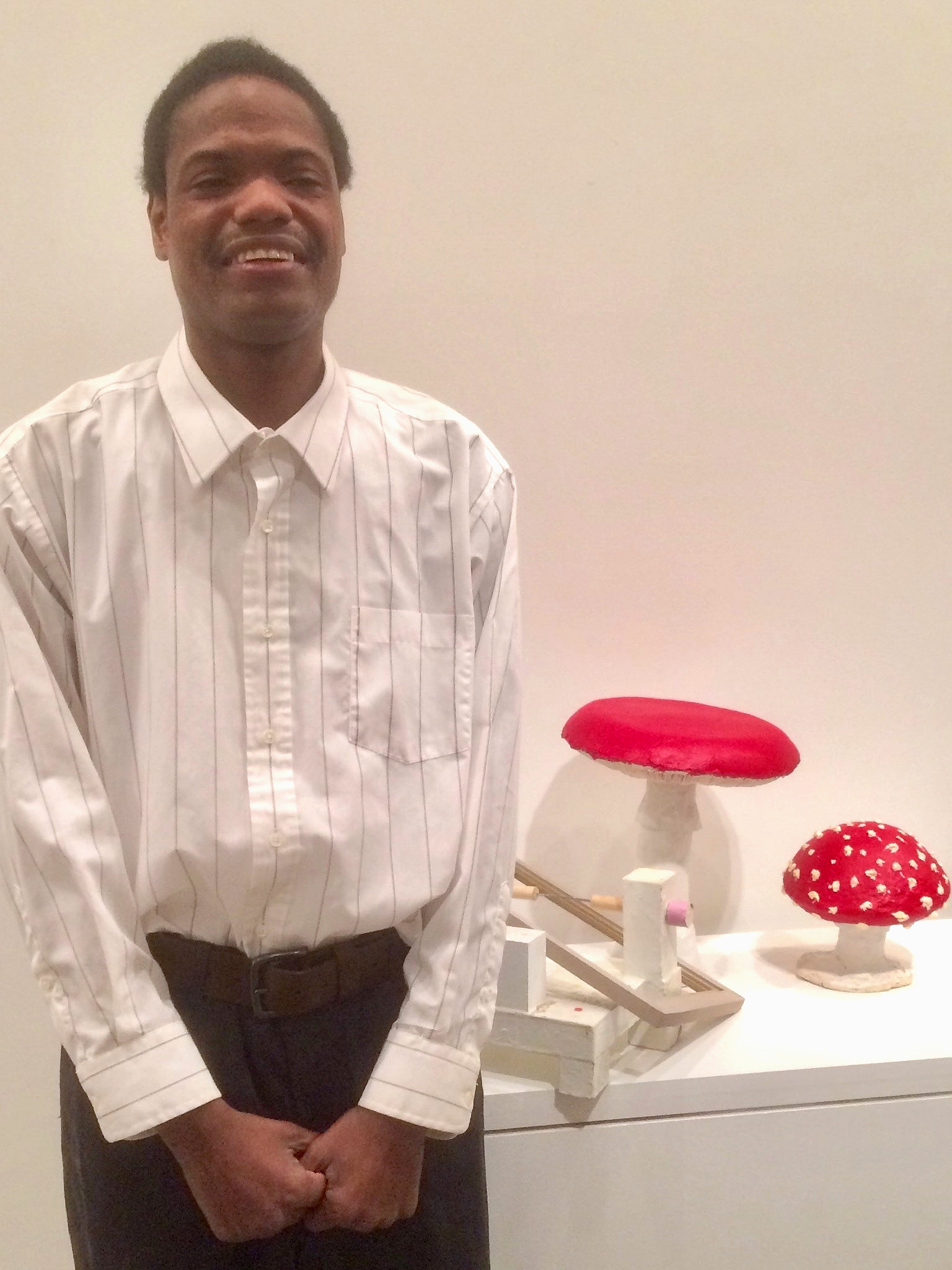 Lawrence wearing a white button-down shirt and standing next to his red-cap mushroom sculptures at a gallery opening reception. Photo courtesy of the artist.