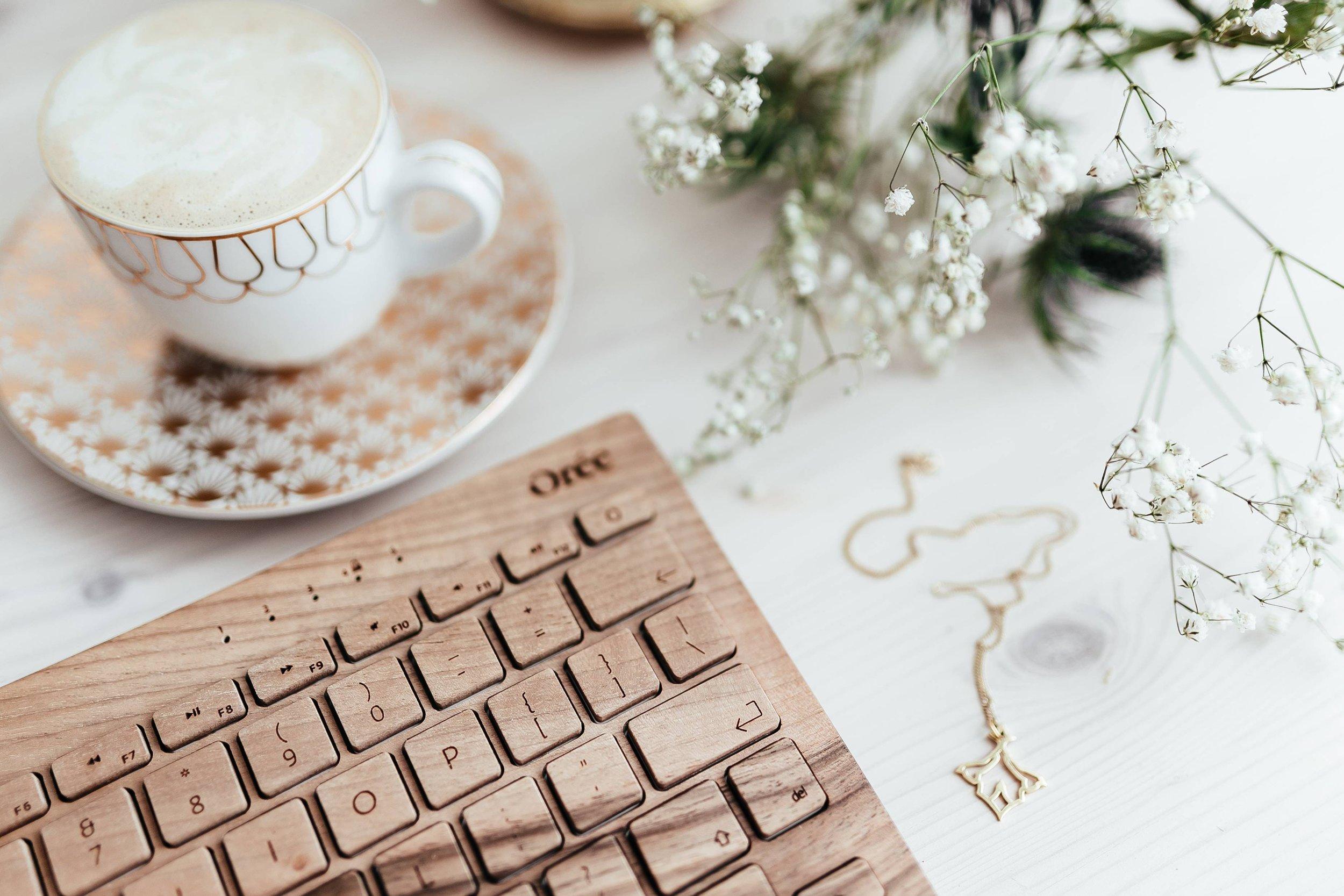 kaboompics_Wooden keyboard, coffee and golden jewellery.jpg