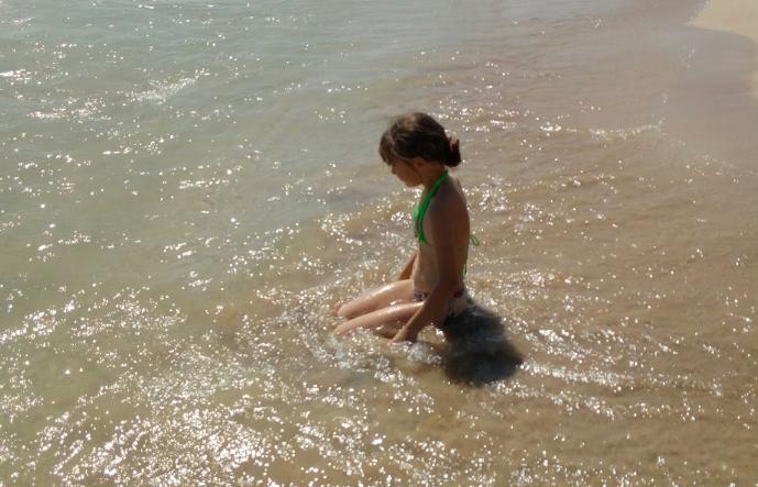 strand meisje zit in water cropped out.jpg