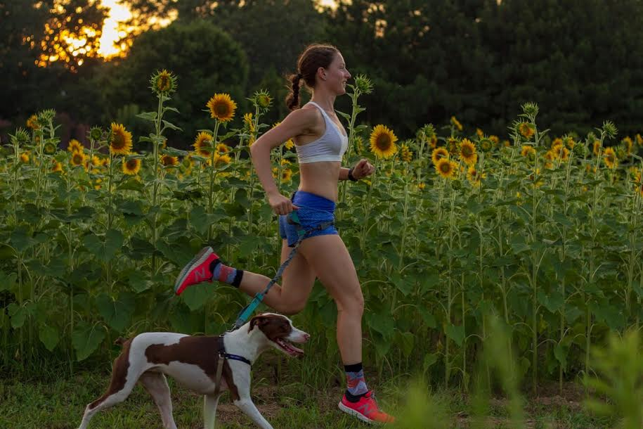 Erin and her dog Charlie running through the sunflower field at Dorothea Dix Park