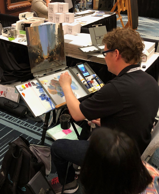 Bryan Mark Taylor Demsontrating the Strada Easel He Invented at the Strada Easel Booth. My husband is the new proud owner of one!