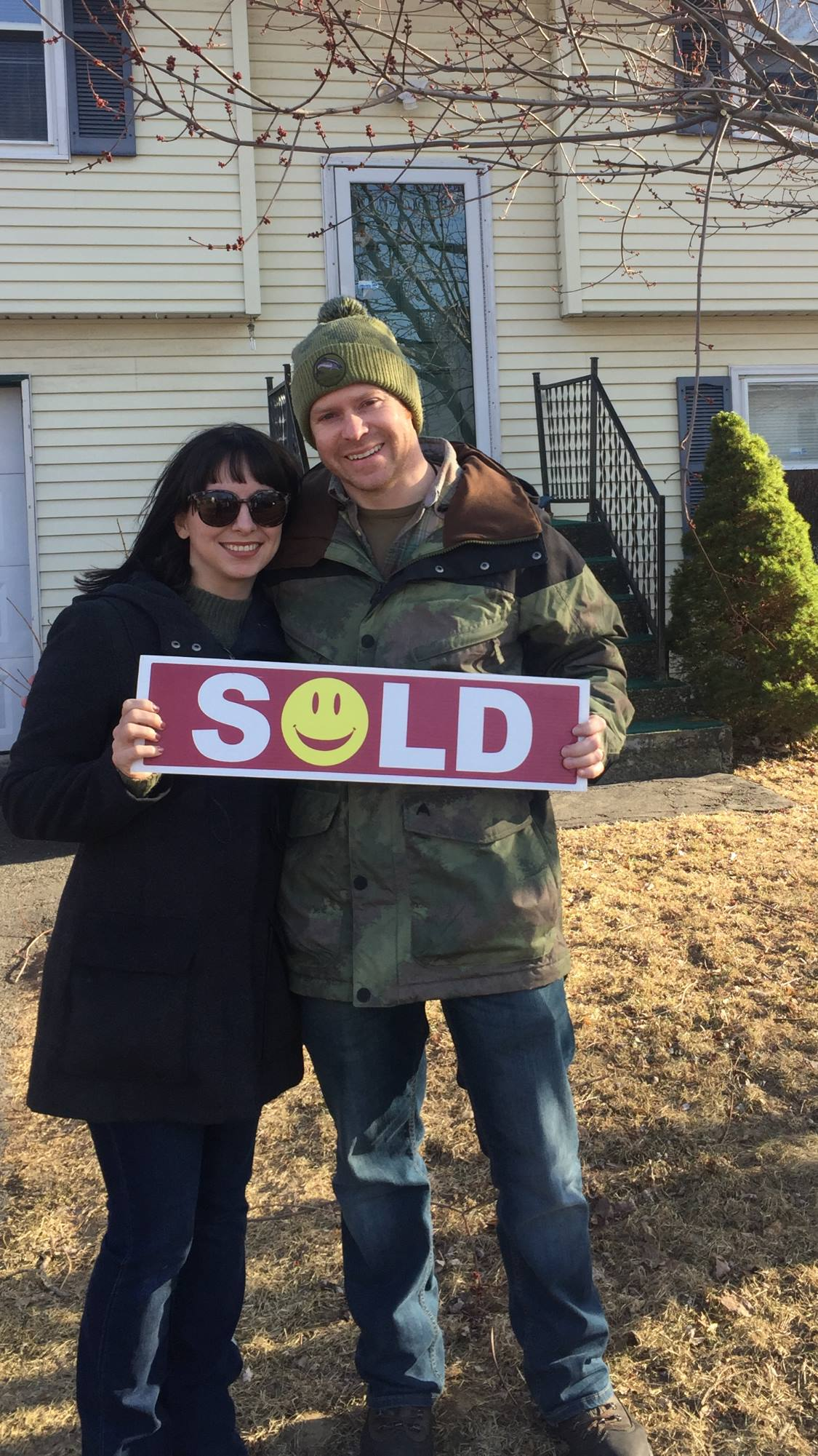 Clients holding a SOLD sign in front of their new home.jpg