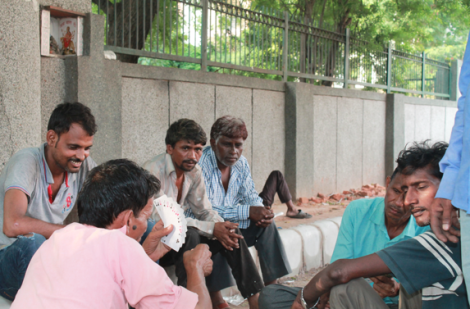 Workers playing cards while waiting for employment at the labour chowk.