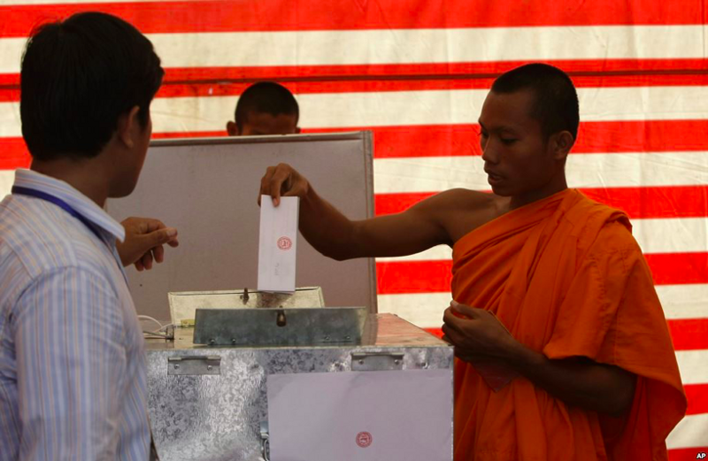 A Cambodian Buddhist monk, right, casts his ballot in local elections at Wat Than pagoda's polling station in Phnom Penh, Cambodia, Sunday, June 3, 2012. Via Associated Press
