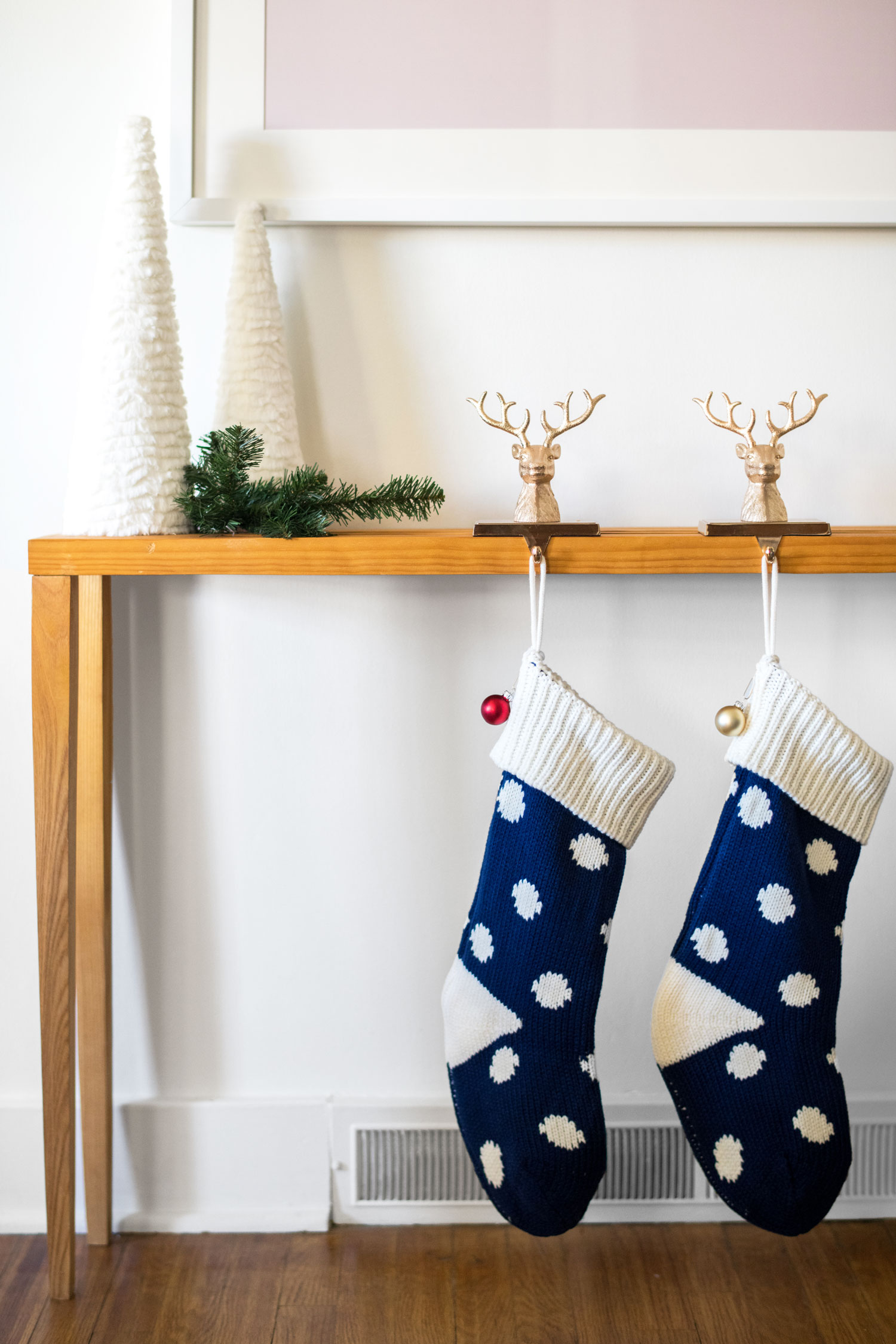 I'm drawn to simple styling when it comes to holiday decor so these white, furry trees and a sprig of faux pine were the perfect touch on this console table. To personalize the stockings, I chose three different colored ornaments and attached them to the sides.