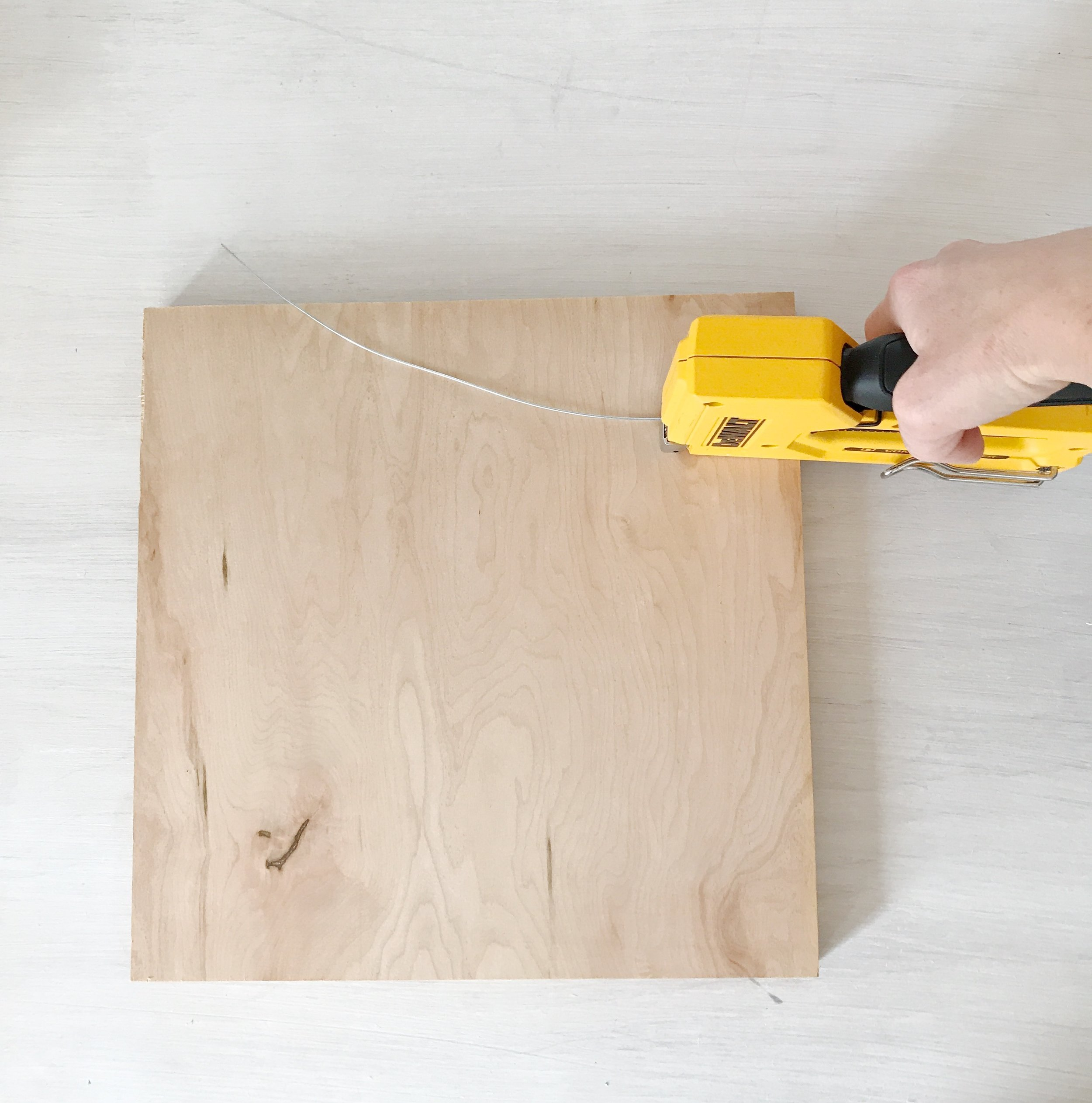 Step 7: Staple wire - Once you have your piece of wire cut for hanging, simply staple it in place on the back of your wooden board.