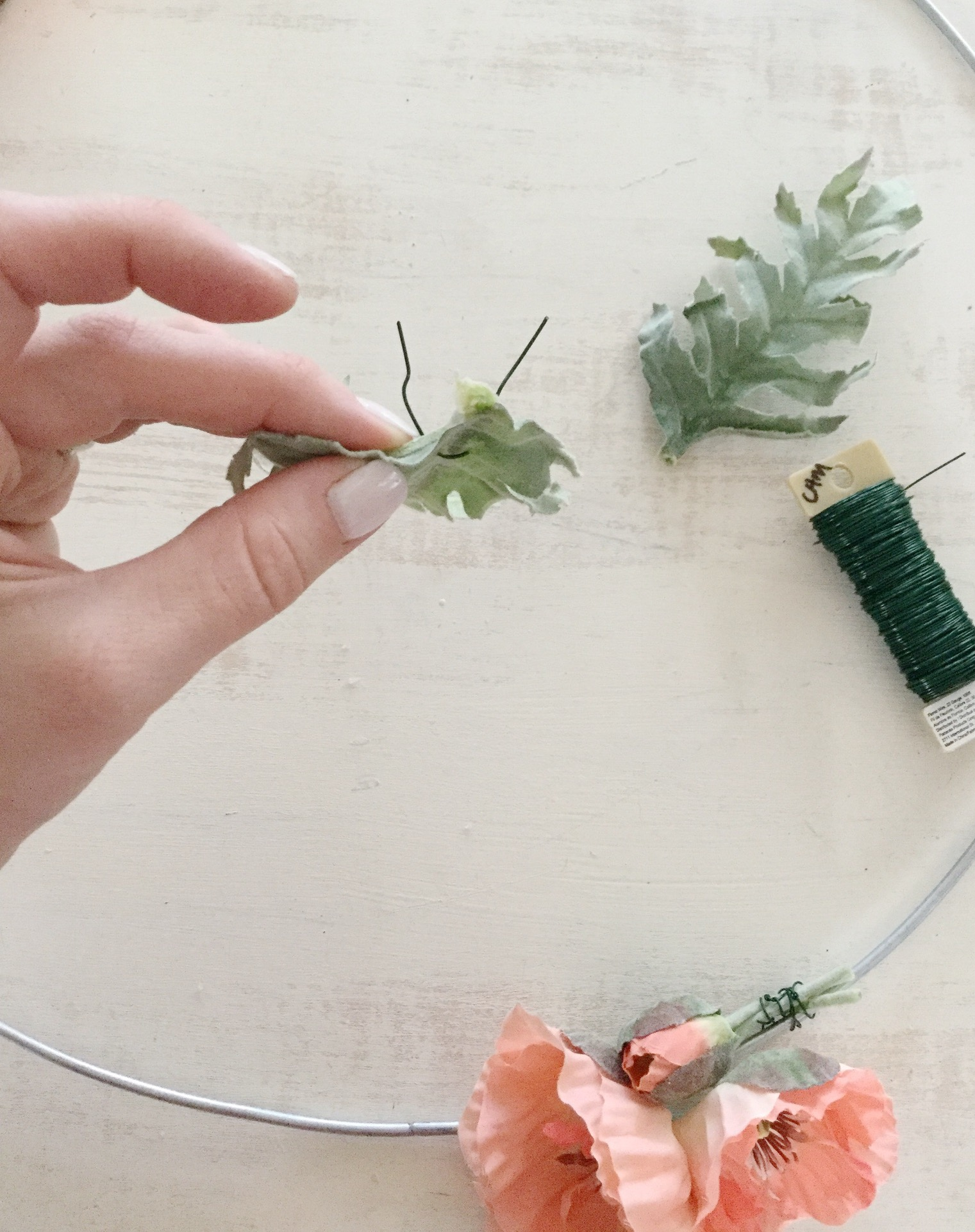 Step 4: Add greenery - This step is optional as you may choose flowers that stand well alone. However, if you have leaves or other greenery you want add, simply poke a piece of floral wire through the leaves so that the wire loops over the spine of the each leaf.