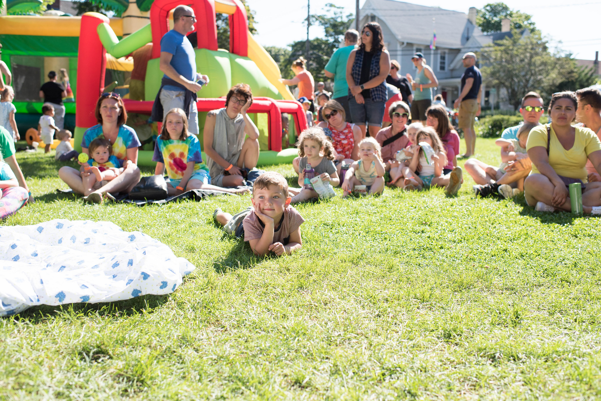 A group of families sitting on grass in front of a bouncehouse at Littles