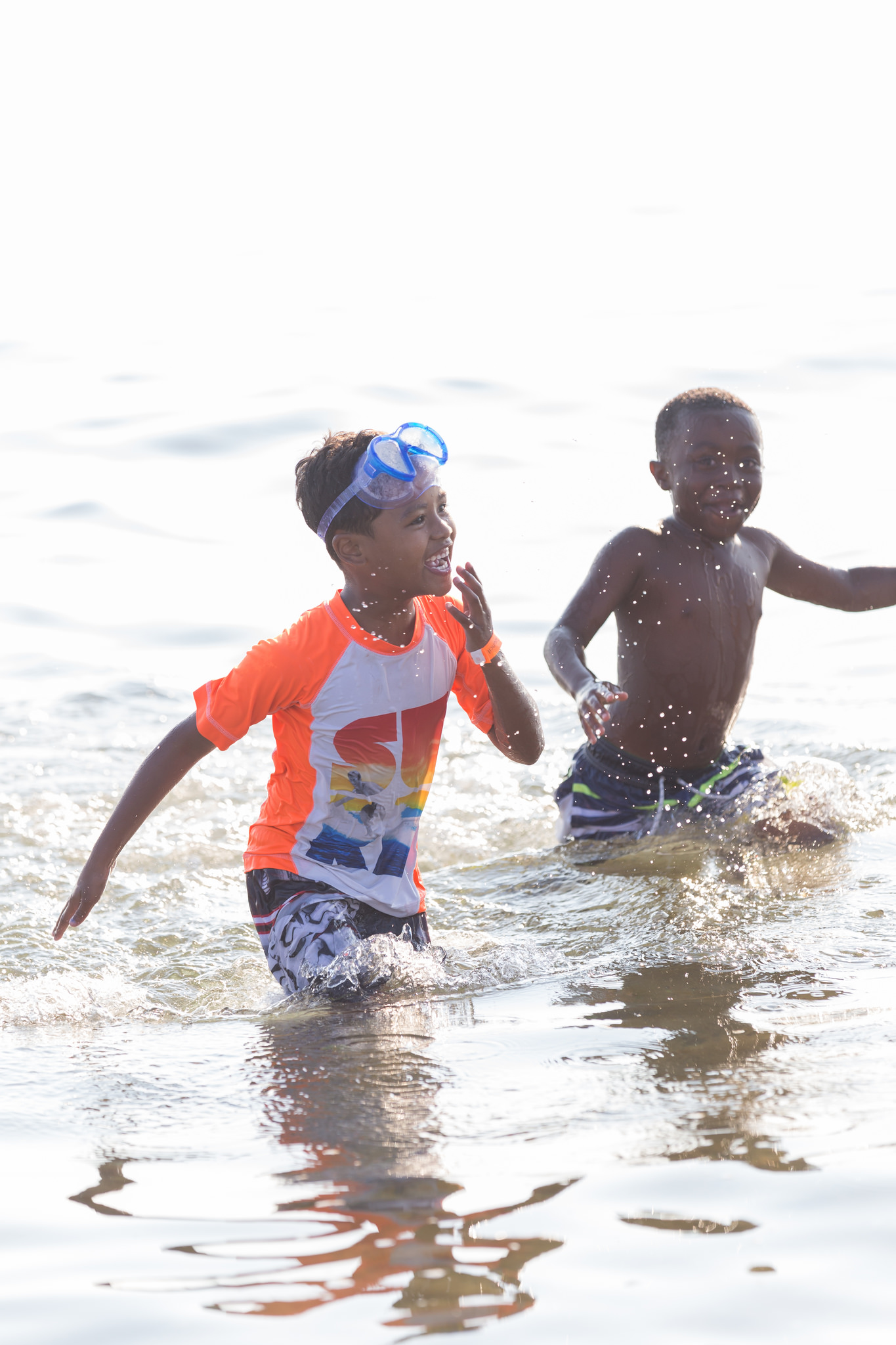 Two kiddos splashing through the ocean