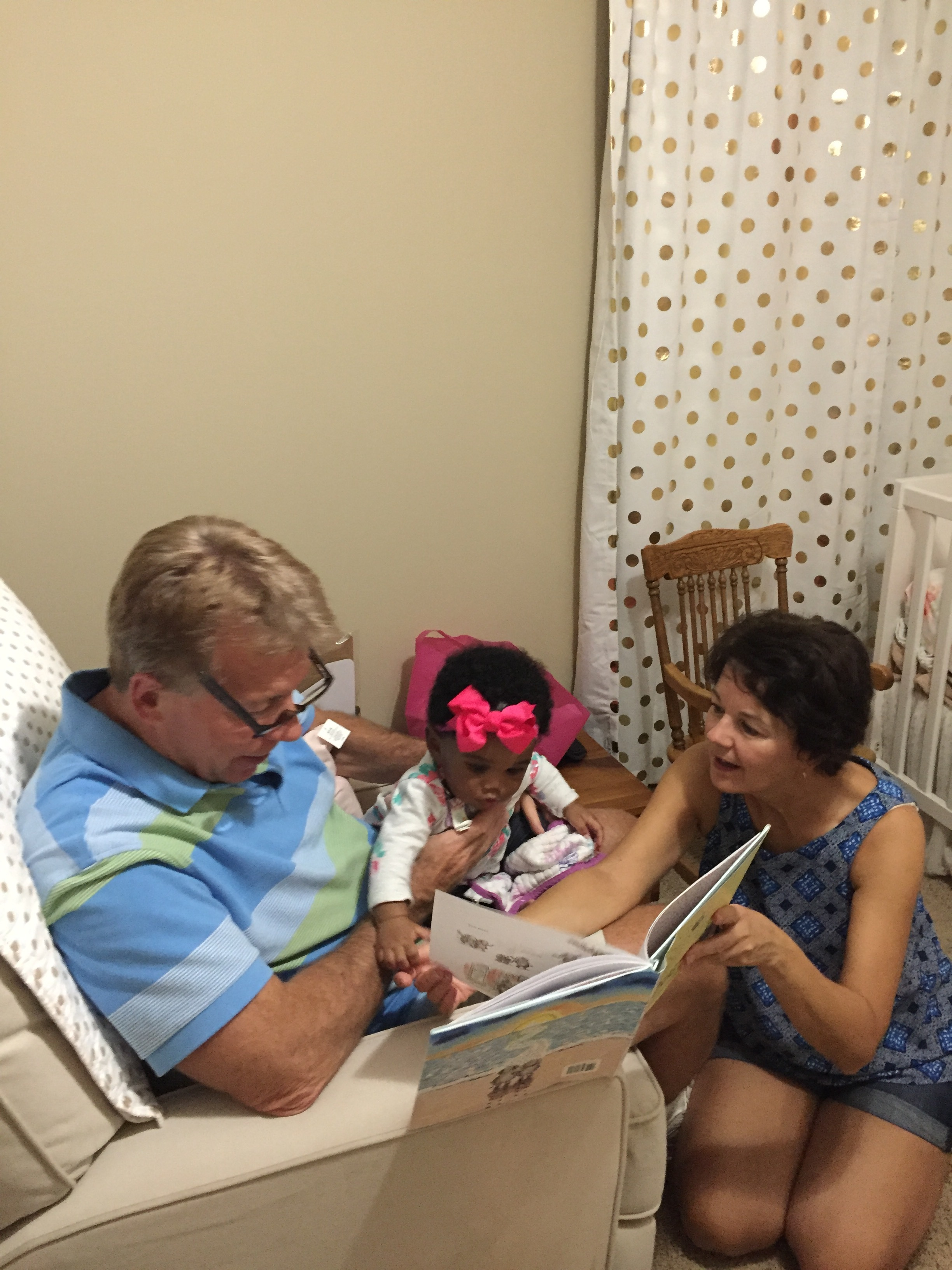 Baby Evie reading with Gigi and Grandpa