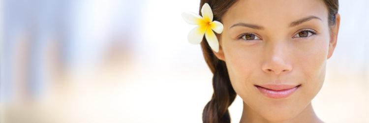 Beautiful woman with frangipani in her hair