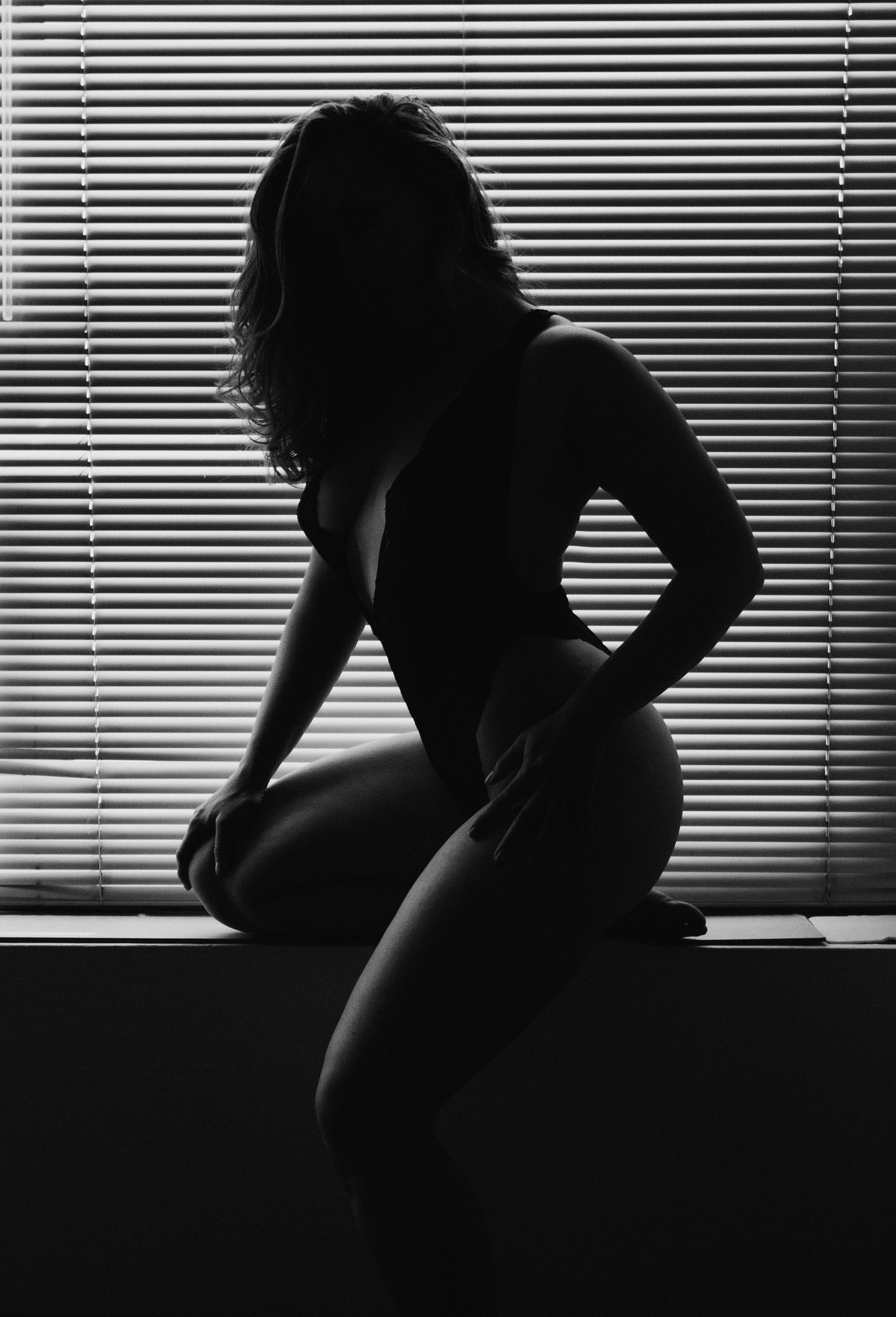 boudoir portrait of woman in black lace bodysuit silhouetted in front of miniblinds