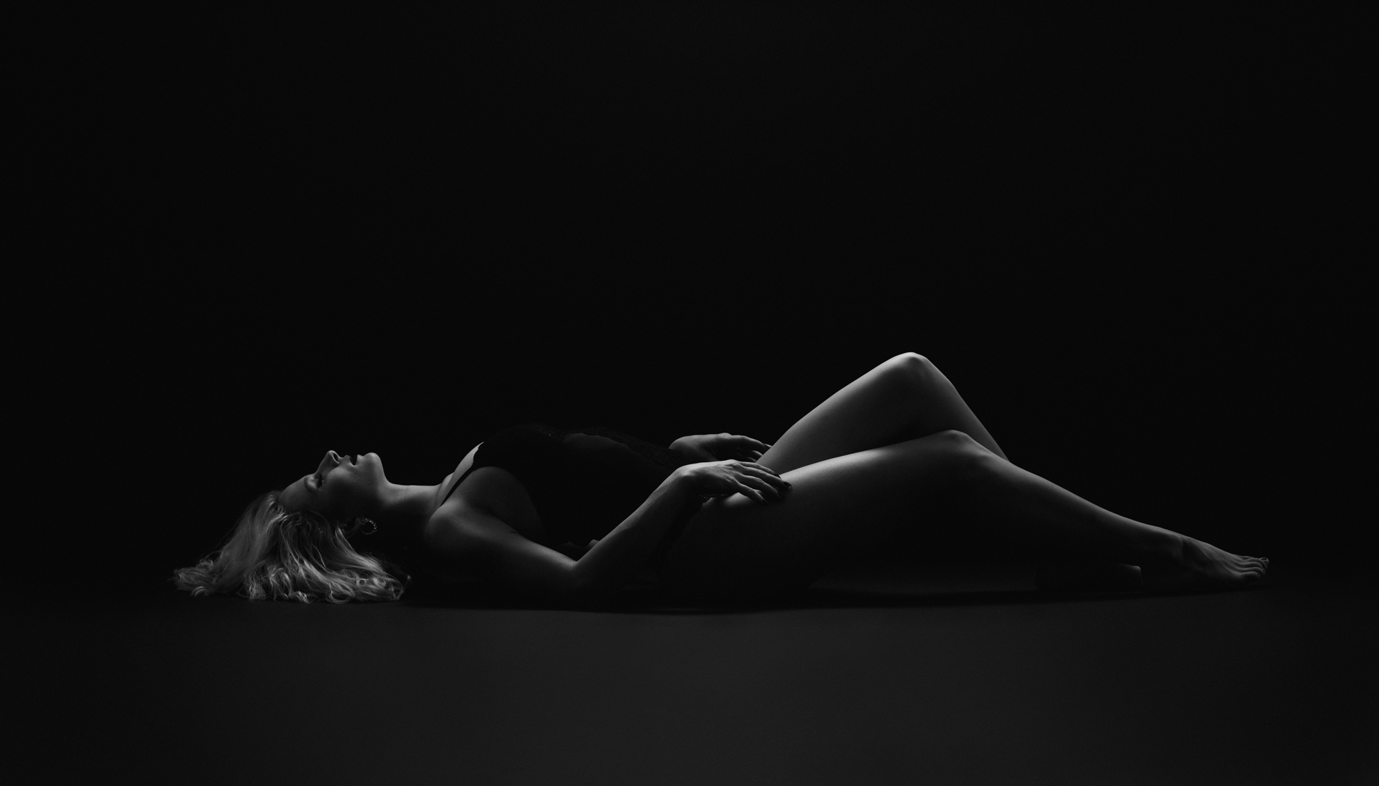 Blonde woman in black bodysuit lying on back with knees bent and hands on thighs
