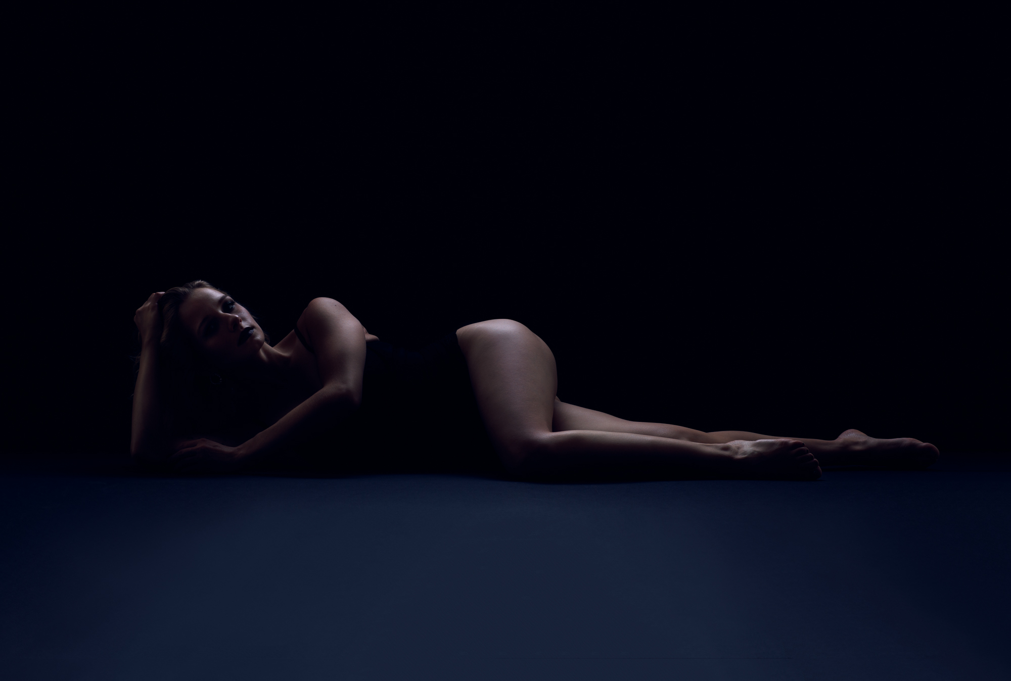 Moody bluish tones with woman lying on her side with her head propped up by her right hand.