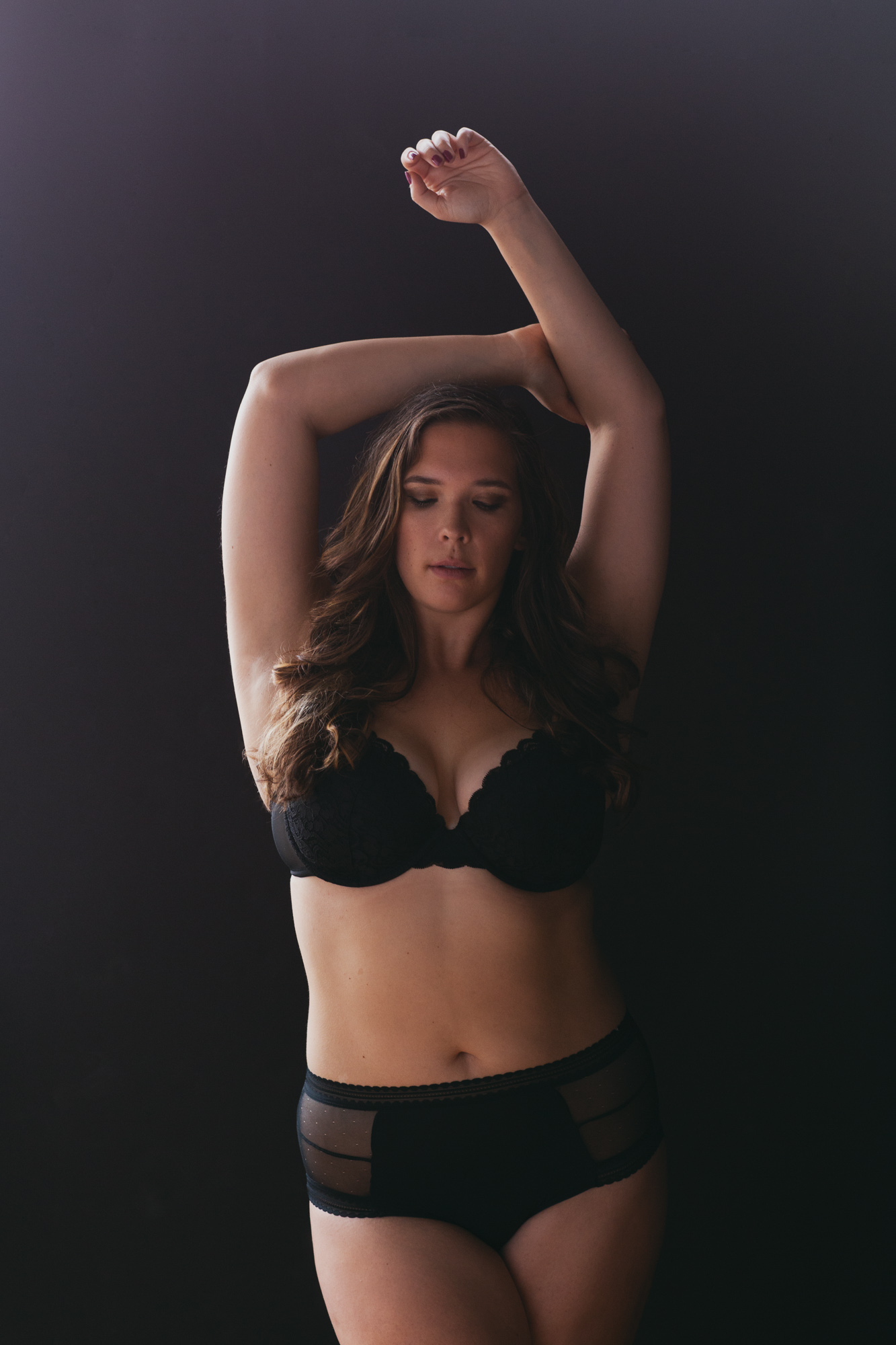 Brunette in black bra and panty set with arms above head