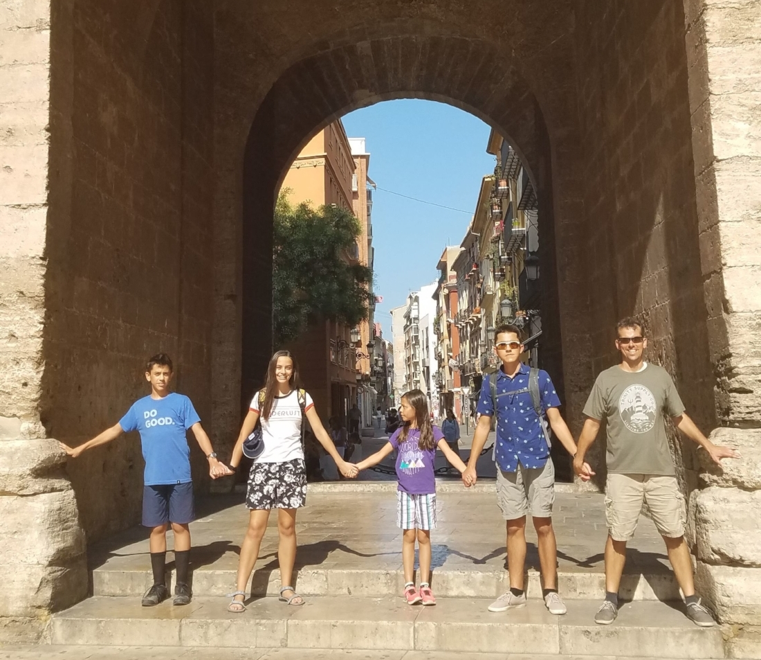 Our family holding hands at the base of Torres de Quart