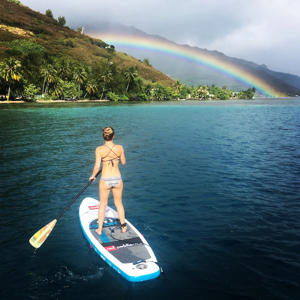 Connie paddle boarding into a rainbow on the island of Moorea.
