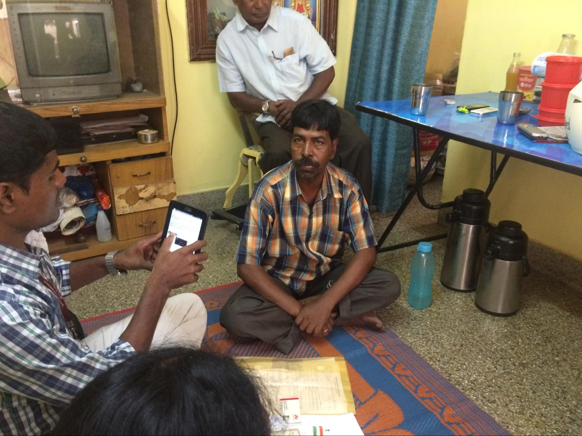 An agent helps a microentrepreneur apply for a loan in India