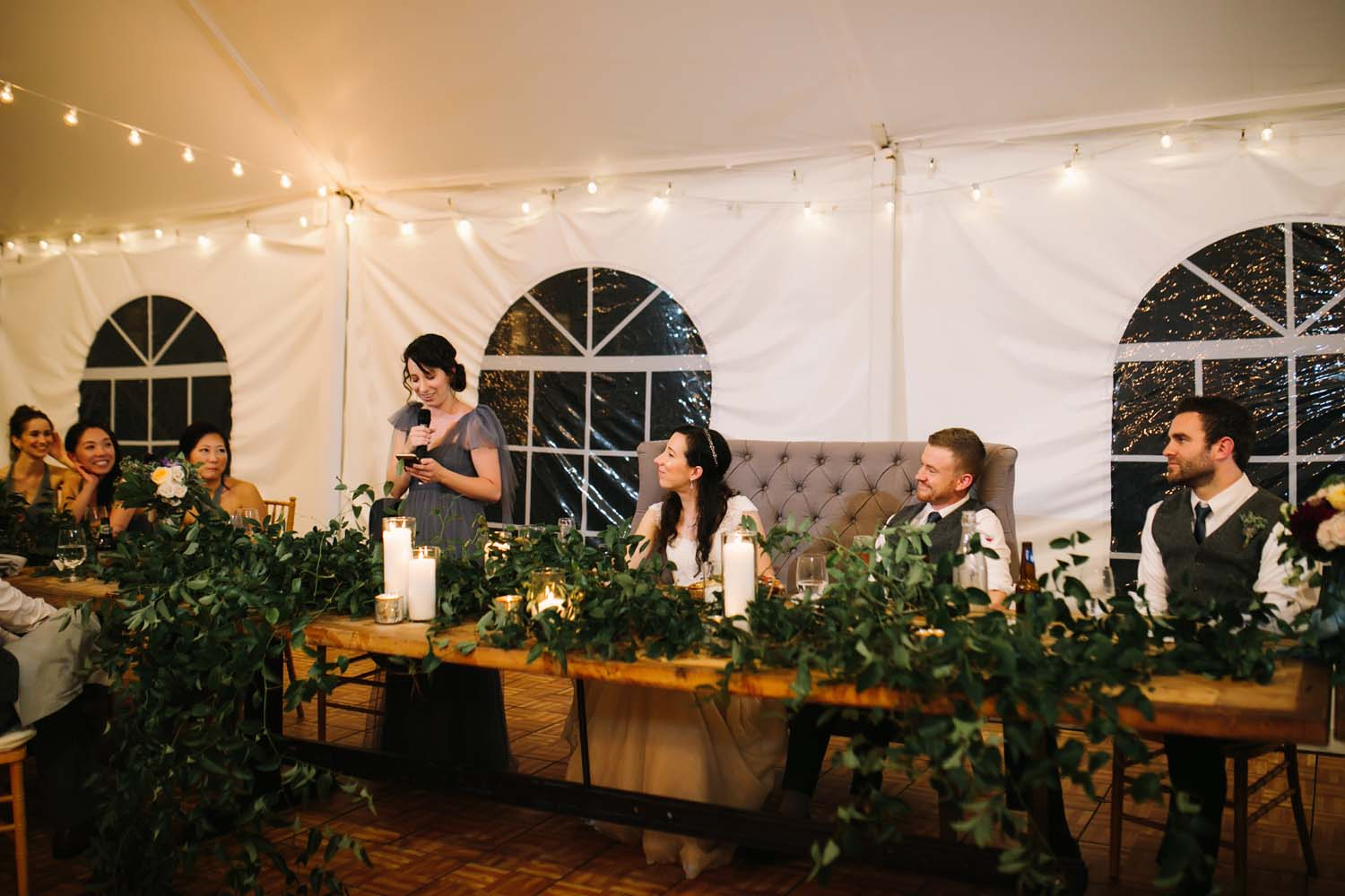 head table in green smilax with candles