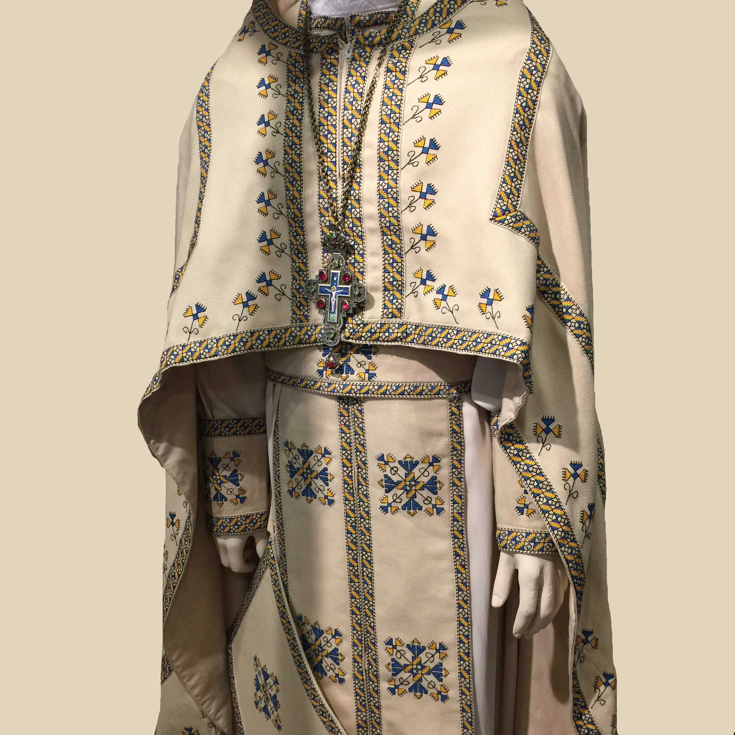 Liturgical Vestments Богослужбове Облачення - The priest's vestments include a Dalmatic, which is a long, light-coloured robe with narrow sleeves. Maniples (cuffs) are worn at the wrist. The Epitrachelion (stole), which goes around the neck with the two ends hanging down evenly in front, symbolizes the priest's consecration and is tied with a Zone (ecclesiastical belt) at the waist. The Chasuble is a long, sleeveless cloak, shortened in front.