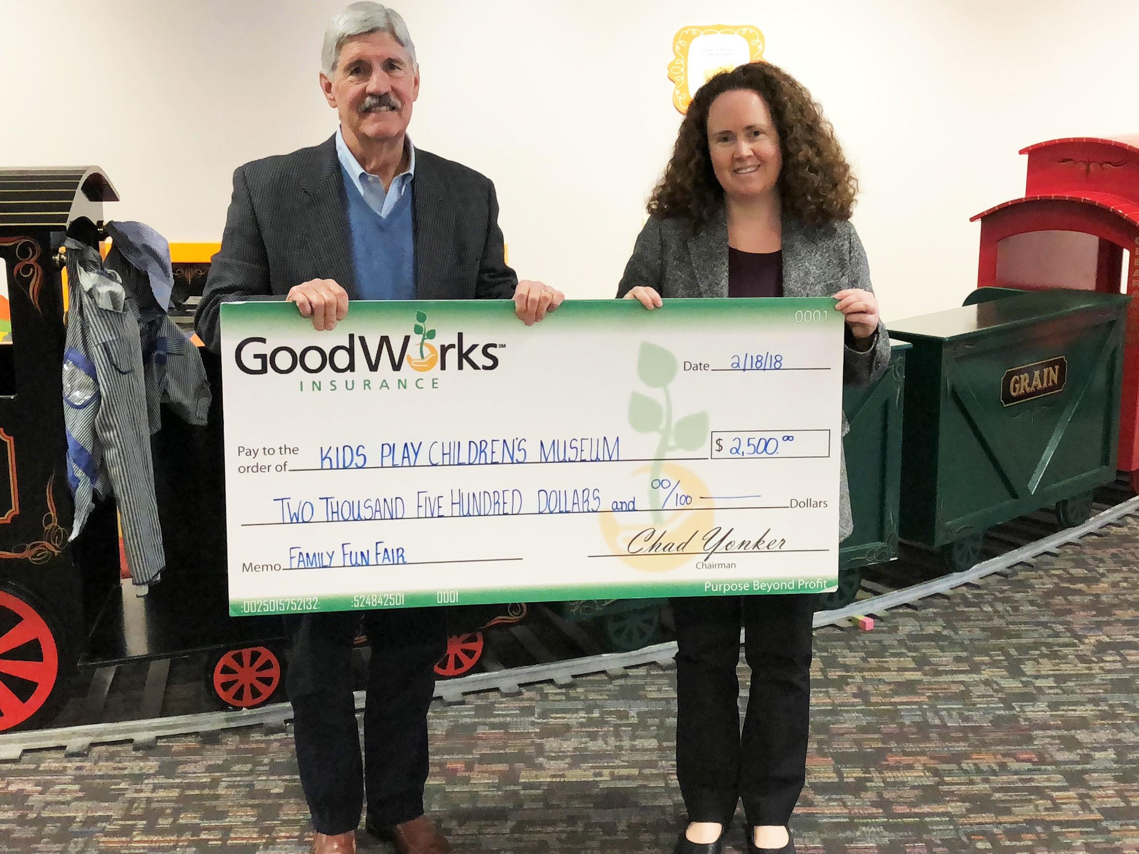 Edward F. Ryan, senior vice president with GoodWorks Insurance, presents check to Eileen Marriott, KidsPlay Children's Museum director.