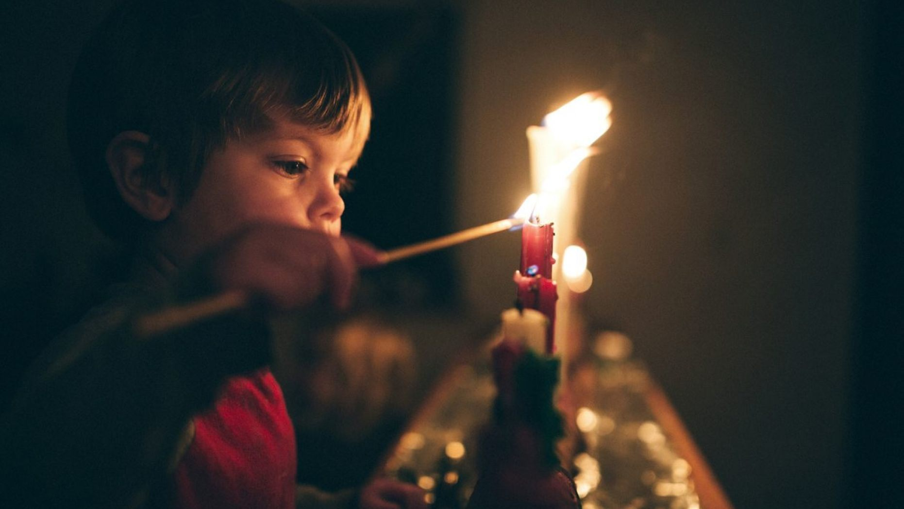 Little boy lighting Christmas candles