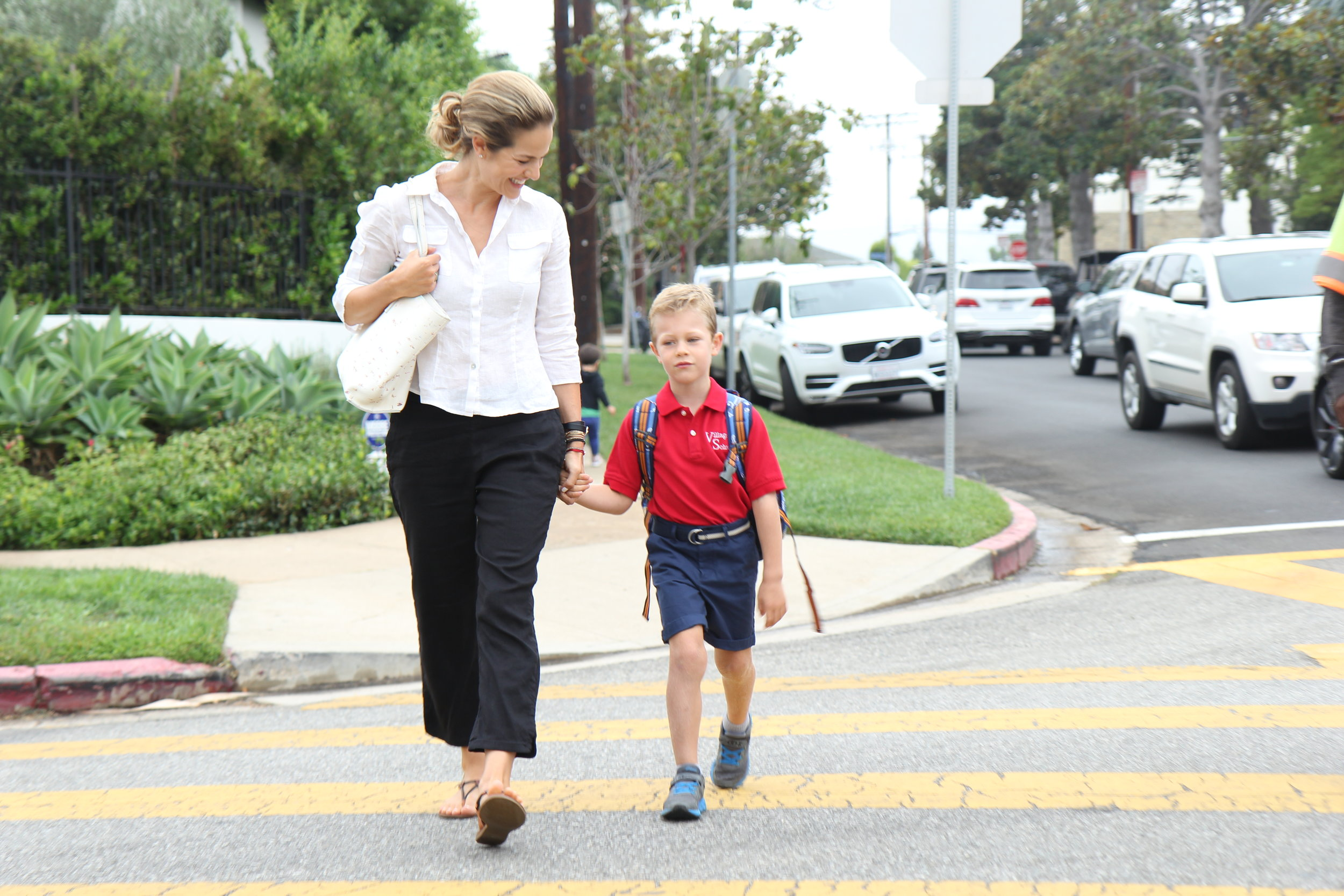 Zelana Montminy walking with son across street