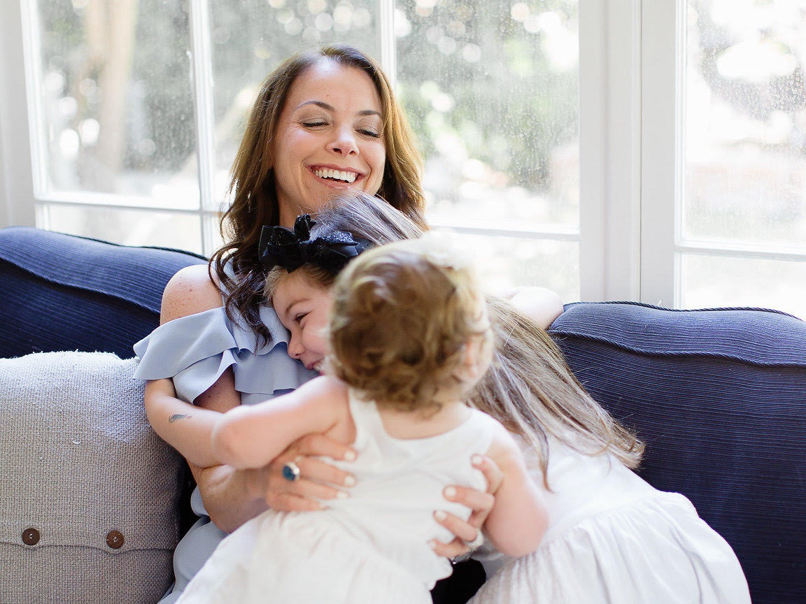 Mom hugging two daughters on couch Credit: Hylah Hedgepeth