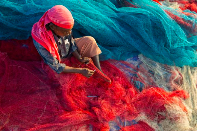 A fisherman in Kerala, India, repairs nets on a beach. Plastic pollution can damage and clog nets, but now fishermen are fighting back.  PHOTOGRAPH BY FRANK BIENEWALD, GETTY IMAGES