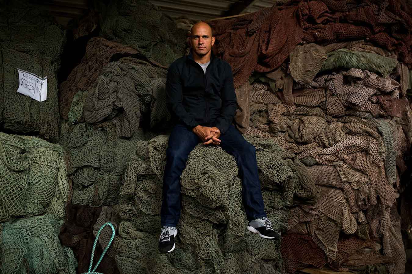 Kelly Slater sits on top of recycled fishing nets on a factory visit in Slovenia. Photo: Todd Glaser
