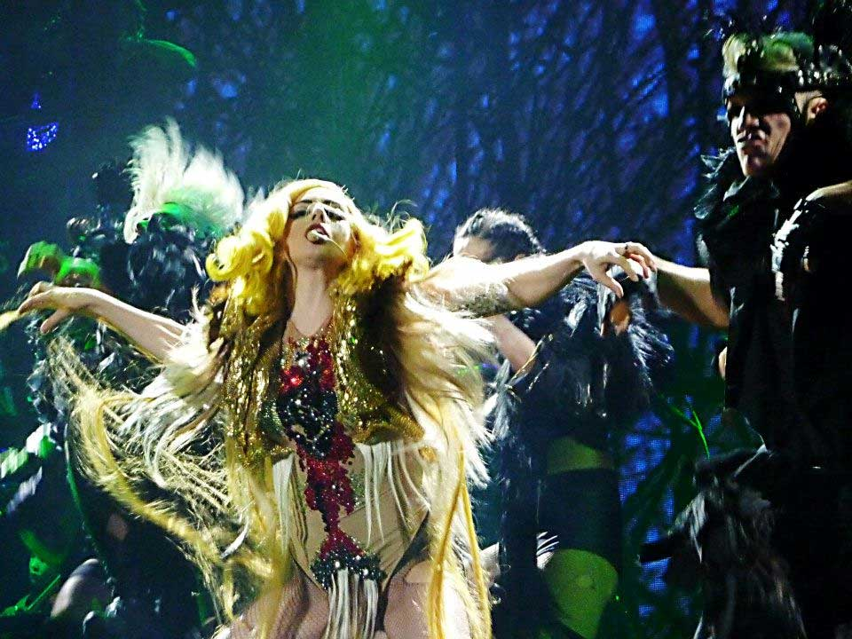 Lady Gaga wears Alex's Sacred Heart Chimera, a flesh body suit with a Swarovski diamond heart on the chest, hairy crotch and chest areas, feathered shoulders and a long hair cape and golden hood.