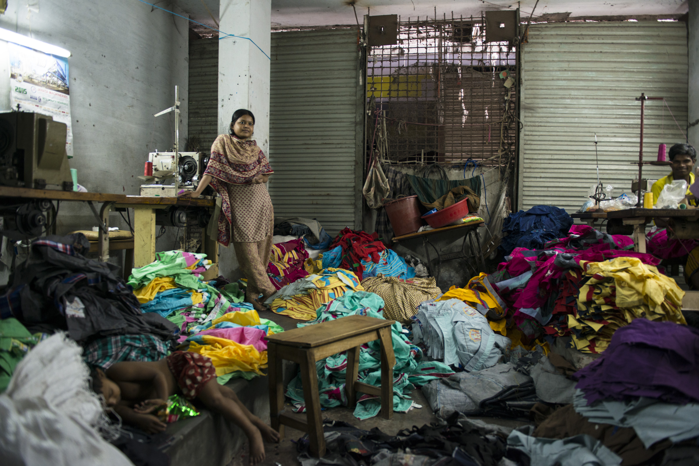 A female garment worker stands amidst children clothes. Due to a lack of child care facilities most young children spend their time with their mother at the workplace. Picture: Claudio Montesano Casillas.