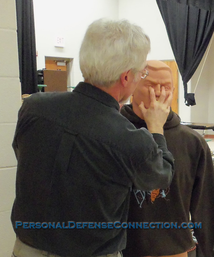 Demonstrating a a self defense technique, the eye gouge.