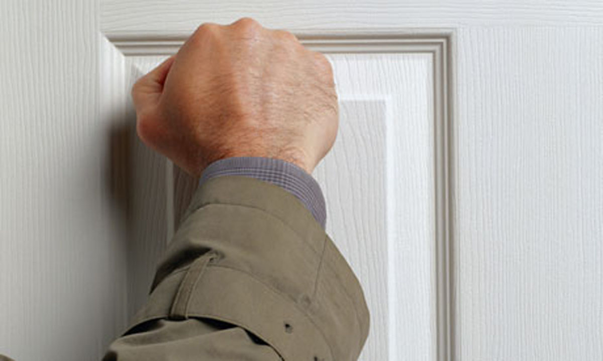 Photo of hand knocking on a door for No Stranger Gets in Your House. Ever. Blog - Personal Defense Connection