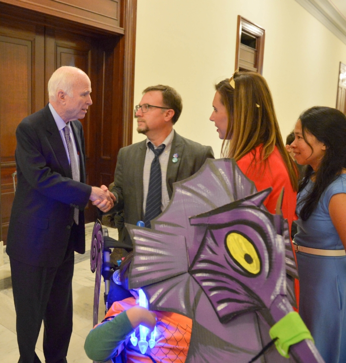 "My husband Brian shaking hands with Senator McCain. This is Brian's ""wow"" face. Because, wow. Also, it was Halloween and we went trick-or-treating in the Senate (as one does) and that is a giant seahorse costume we made for Simon's wheelchair. He was Aquaman. I don't always wear a Wonder Woman crown, just as needed. I'm thinking about keeping it in my handbag..."