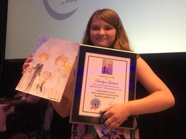 "Image Description: Abby's sister Bridget with her award from NCIL and her award-winning artwork about ""What the DIA Means to Me."""