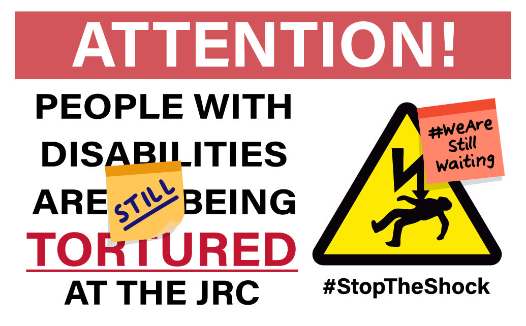"[Image description: An illustration of a construction site-style metal warning sign. At the top, white text on a red background reads: ATTENTION! Below that is large text which reads: ""PEOPLE WITH DISABILITIES ARE STILL BEING TORTURED AT THE JRC."" Next to the text is a warning symbol depicting a person being electrocuted against a yellow triangle background. Below the warning symbol is text reading #StopTheShock. There is a post-it note on the sign that says #WeAreStillWaiting.]"